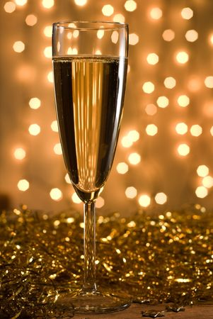 Champagne flute among golden ribbons, defocused lights background - shallow DOF, selective focus on the glass. photo