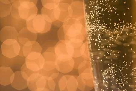 Glass of champagne or beer detail against defocused lights background. Shallow dof - selective focus on some of the bubbles. photo