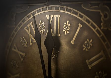 12 oclock: Old clock with roman numerals. Selective focus on  number XII and minute hand. Intentional vignetting. Stock Photo