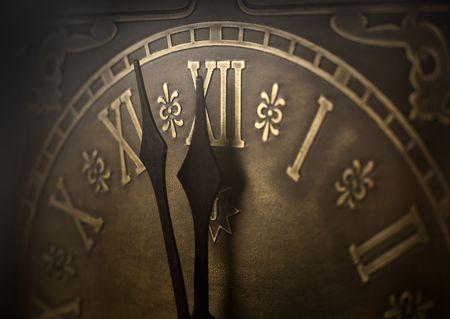 romeinse cijfers: Oude klok met Romeinse cijfers. Selectieve aandacht op nummer XII en minutenwijzer. Opzettelijke vignettering.