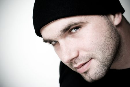 the seducer: Portrait of young man wearing beanie - selective focus on the models eyes.