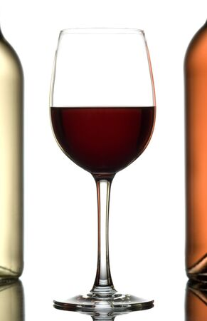 pinkish: Glass of wine between two bottles of wine isolated on white.