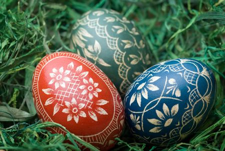 Three handmade easter eggs on the green hay. Selective focus, shallow depth of field. photo