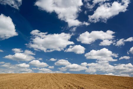 ploughed: Blue sky with clouds over ploughed field. Stock Photo