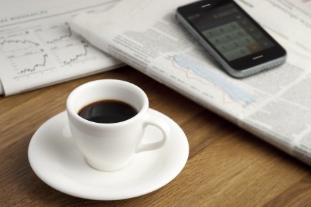 Coffee cup, smartphone and business newspapers with charts  photo