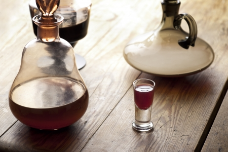 carafe: Old antique carafe and glass of liqueur.  Traditional Polish aged nalewka. Stock Photo