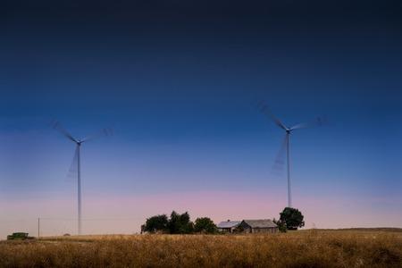 windfarm: Parque E�lico casa adn - Spinning aerogeneradores en el campo al atardecer. Foto de archivo