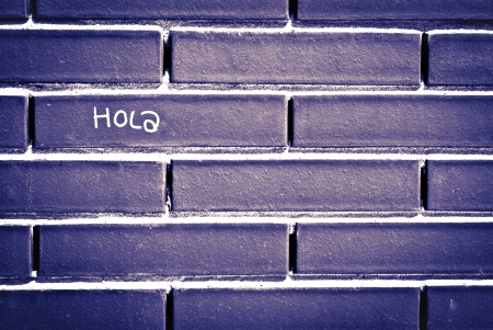 Spanish hello word  write in a wall brick photo