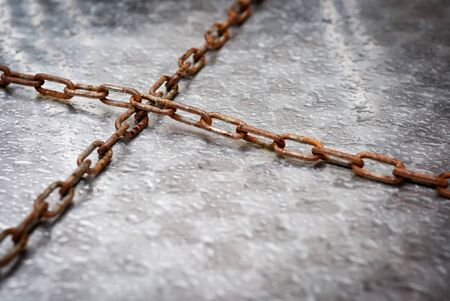 Crossed rusty chains on wet table photo