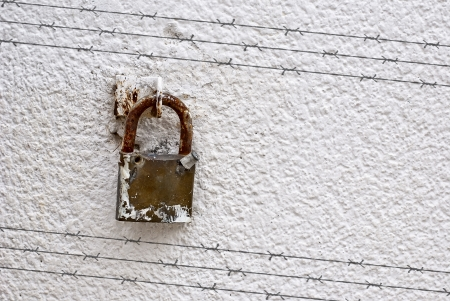 Shadow of barbed wire on wall with padlock Stock Photo - 24768411