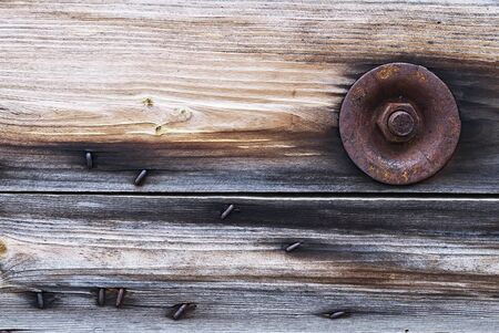 Rusty bolt fastening wooden shield photo