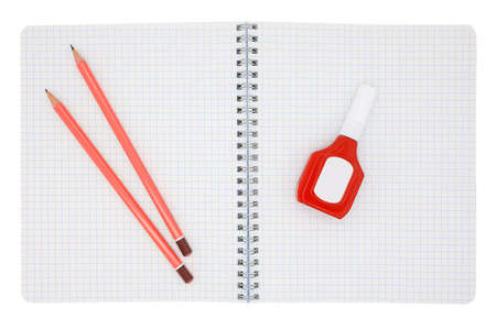 Pencils and error corrector on a school notebook in a cage isolated on a white background Stockfoto