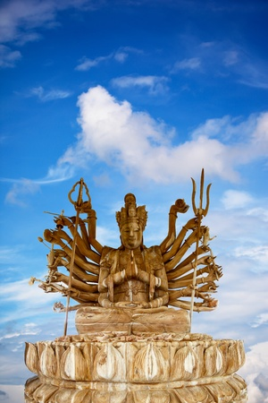 Wood Statue of Guan Yin  isolated on blue sky background photo