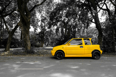 Yellow mini car on the street with the black and white background Editorial