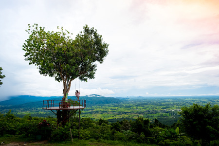 Single woman swing on heart shape tree and natural field with mountain background at Noen-Maprang ,Phitsanulok Province,Thailand Stock Photo