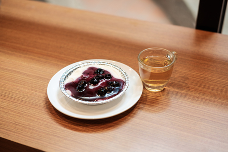Blueberry cheese cake with chinese green tea on the wooden table Stock Photo