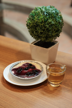 Blueberry cheese cake with chinese green tea and artificial plant  on the wooden table Stock Photo