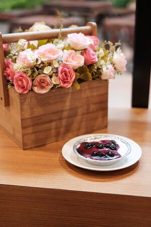 Blueberry cheese cake with artificial flower bouquet on the wooden table
