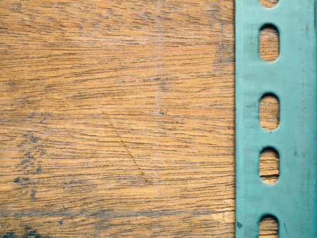 slotted: Slotted angle metal plate over the wooden background