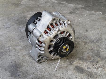 alternator: Old alternator for the car on concrete floor Stock Photo