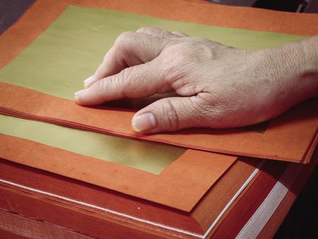 sacrificio: Mano de la mujer mayor es plegable de papel de oro chino para hacer sacrificios a los dioses, efecto de la vendimia