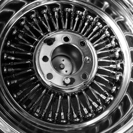 mag: Part of rusty chrome retro wire spoke mag wheel (back view), black and white effect Stock Photo