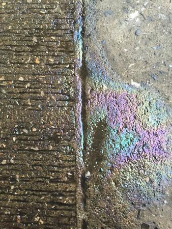 sheen: Oil leak, rainbow sheen on the ground Stock Photo