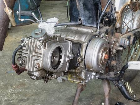 motorcycle repair shop: Old rusty motorcycle engine in bike repair shop Stock Photo