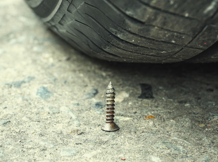 tyre tread: Sharpen metal screw nail nearly to puncture into wheel tire, selective focus (colored filter effect) Stock Photo