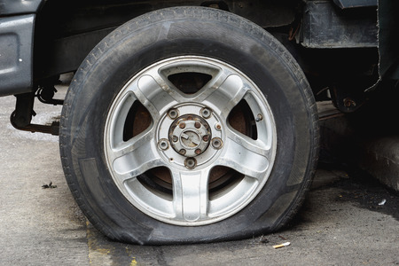 flat tire: Damaged flat tire of an old car on the road