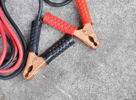 12v: Black and red copper clamp with jumper cable for car battery charging, selective focus