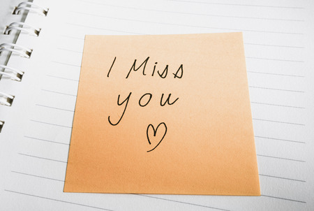 i miss you: Handwritten I miss you word and heart shape on sticky note, in opened notebook. Colored filter effect.