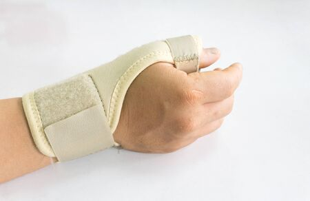 carpal tunnel: Elastic wrist support brace band wrap on hand to relieve pain, selective focus
