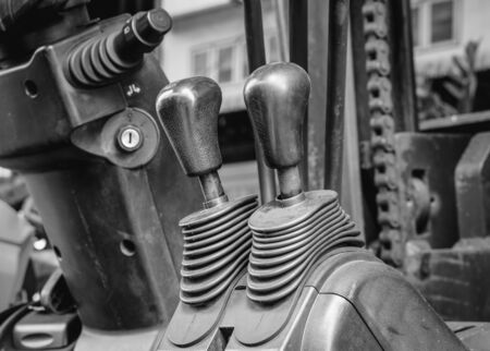 center position: Old and dirty forklift operating levers control, selective focus (black and white effect) Stock Photo