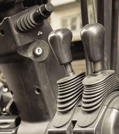 center position: Old and dirty forklift operating levers control, selective focus