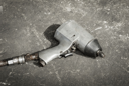 llave de sol: Old used pneumatic impact wrench on concrete floor in the sun with vintage effect