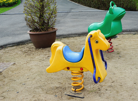 totter: Old colorful seesaw in sand public playground