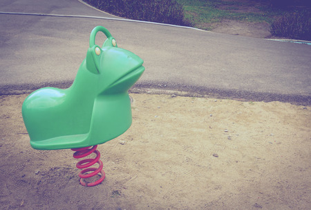 totter: Old colorful seesaw in sand public playground with vintage effect