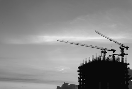 Silhouette of industrial cranes and building construction with black and white effect  Stock Photo