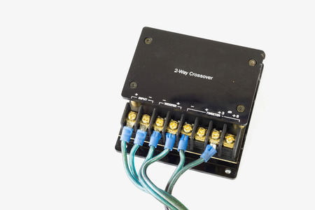 Old black passive crossover network for car audio on white background