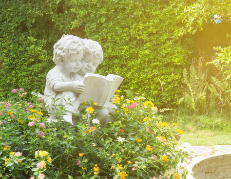 Sculpture of boy and girl reading the book in public garden Stock Photo