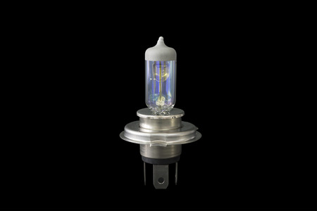 Old used car halogen light bulb isolated on black background