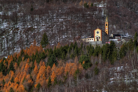 The village of Hat, municipality of Garessio, Piedmont, Italy, with its church, on the side of the mountain, surrounded by woods and the first snow.