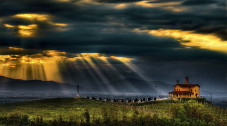 Spectacular blades of light filter through the dramatic clouds that dominate the Partisan Shrine of Bastia Mondovi ', in the Langhe, Piedmont, Italy.