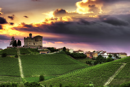 A spectacular sunset over the village of Grinzane Cavour with its castle (UNESCO WHS) surrounded by vineyards in the Langhe, Piedmont.