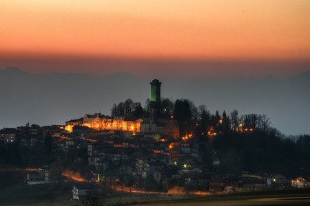 Night falls on Murazzano and its medieval watchtower in the Langhe, Cuneo province, Piedmont, North Italy. Banco de Imagens