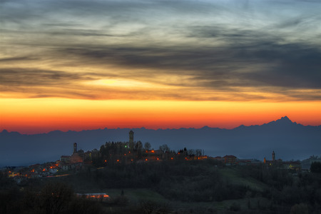 Langhe - A burning sky, at nightfall, draws the skyline of the Alps, with the soaring Monviso, while in the town of Murazzano the lights are lit. Cuneo province, Piedmont, North Italy.