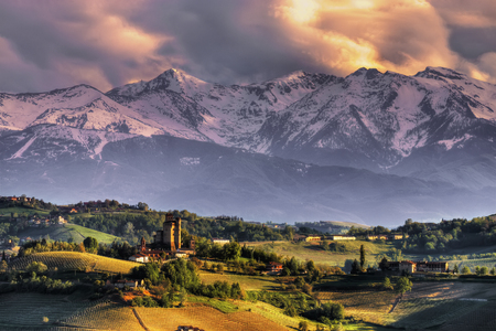 The castle of Serralunga d'Alba, with the background of the Alps, at sunset. We are in the Langhe, Cuneo province, Piedmont, North Italy. UNESCO World Heritage Site.