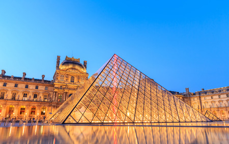 PARIS, FRANCE - JULY 19: The Louvre Pyramid at dusk during the Michelangelo Pistoletto Exhibition on July 19, 2014 in Paris. The Pyramid is the main entrance to the Louvre Museum.