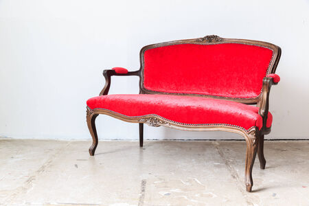 red sofa: Red vintage sofa on white wall. Stock Photo
